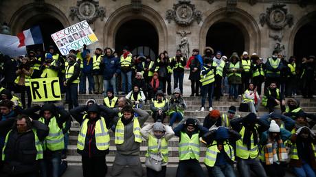 Des Gilets jaunes mains sur la tête en référence à l'arrestation de lycéens, devant l'Opéra Garnier à Paris, le 15 décembre.