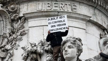 Un homme brandit une pancarte où est inscrit