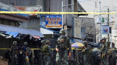 Des membres des forces de l'ordre devant l'église où deux bombes ont explosé, le 27 janvier 2019 à Jolo aux Philippines.