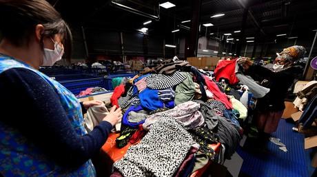 Des employées trient des vêtements usagés dans un centre de recyclage de la coopérative Le Relais à Bordeaux, le 23 janvier 2019. Le Relais est une société coopérative et participative regroupant des entreprises ayant des valeurs sociales dédiées à la collecte et à la réinsertion sociale.