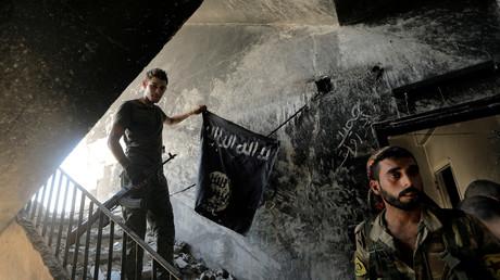 Des combattants des Forces démocratiques syriennes récupèrent un drapeau de l'Etat islamique à Raqqa, le 14 août 2017 (image d'illustration).