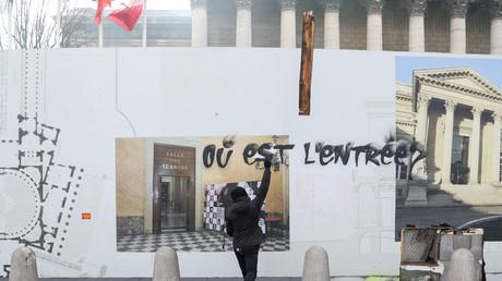 Un protestataire jette un bout de bois derrière les protections, devant l'Assemblée nationale.
