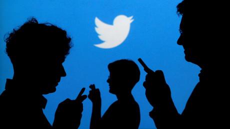 Les ombres de personnes tenant un téléphone portable sont projetées sur une affiche avec le logo Twitter (image d'illustration).