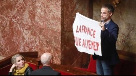 Le député Sébastien Nadot déroulant une banderole dénonçant l'implication de la France dans les crimes de guerre au Yémen le 19 février.