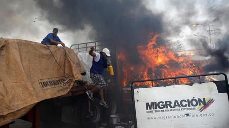 Des partisans de l'opposition déchargent de l'aide humanitaire d'un camion incendié après des affrontements entre les partisans de l'opposition et les forces de sécurité vénézuéliennes sur le pont Francisco de Paula Santander, le long de la frontière entre la Colombie et le Venezuela.