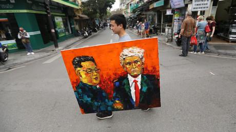 Un homme porte un tableau représentant Kim Jong-un et Donald Trump, à Hanoï, au Vietnam, le 27 février 2019.