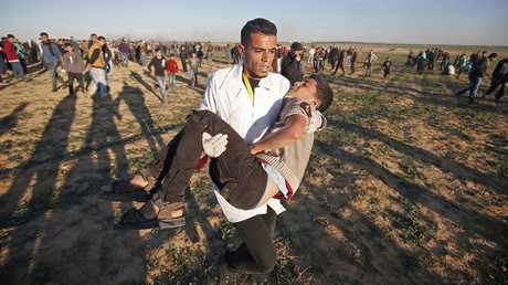 Le 14 décembre 2018, un Palestinien éloigne un jeune homme des lieux de manifestations à la frontière entre Israël et Khan Yunis, dans le sud de la bande de Gaza.