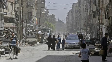 Des Syriens marchent dans une rue de Douma.