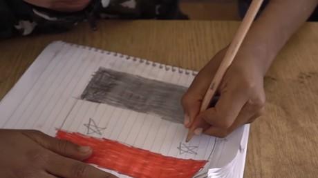 Un enfant syrien dessine le drapeau de son pays.