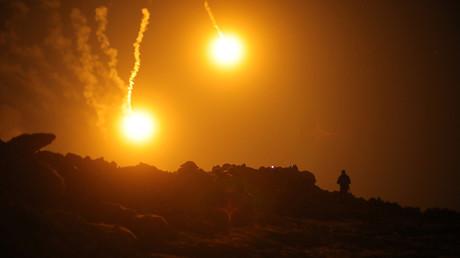 Des fusées éclairantes illuminent le ciel de l'enclave de Baghouz, le 11 mars encore controlée par Daesh.