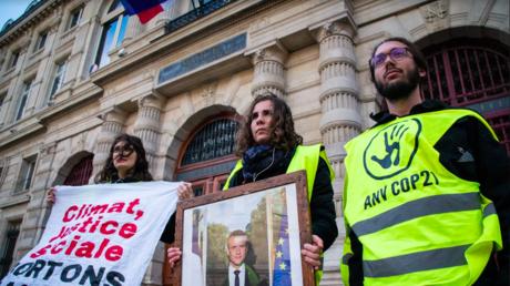 Les activistes d'ANV-COP 21 venant de décrocher un portrait officiel d'Emmanuel Macron.