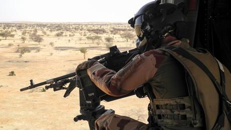 Un soldat français de la mission Barkhane met sa mitraillette en joue  depuis un hélicoptère NH90 entre Gao et Menaka, au Mali, le 21 mars 2019.