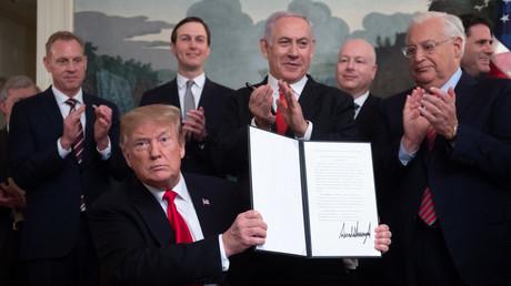 Donad Trump brandissant le décret reconnaissant la souveraineté d'Israël sur le Golan en présence de Benjamin Netanyahu.