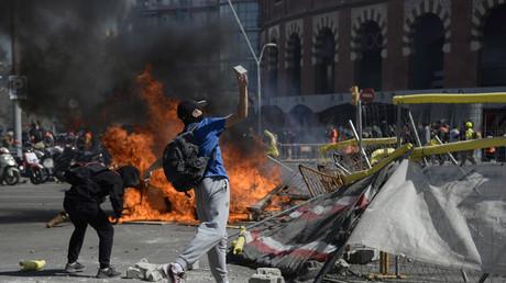 Des contre-manifestants ont érigé une barricade face aux forces de l'ordre  qui protège le rassemblement du parti Vox à Barcelone, le 30 mars.
