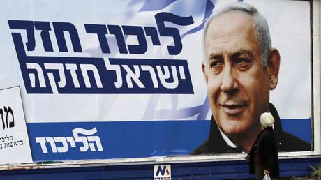Une femme passant devant une affiche de campagne de Benjamin Netanyahou, dans la ville d'Haïfa, le 4 avril 2019, à 5 jours des élections législatives.