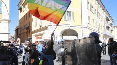 Geneviève Legay, juste avant la charge policière, agite un drapeau coloré orné du mot paix, lors d'une manifestation des Gilets jaunes à Nice le 23 mars 2019.