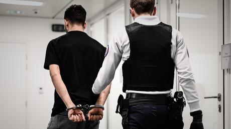 Un policier escorte un homme.