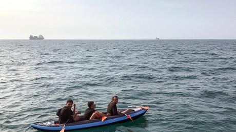 Trois migrants tenant de traverser la Manche depuis la France, au large des côtes de Calais en France, le 4 août 2018 (image d'illustration).