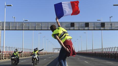 Un Gilet jaune brandit un drapeau tricolore sur le périphérique de Bordeaux, le 17 novembre 2018 (image d'illustration).