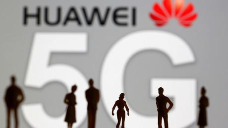 Silhouettes se détachant sur le logo de l'entreprise chinoise Huawei (illustration).