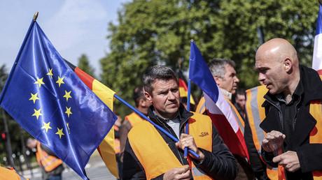 Des producteurs de betteraves arborent des drapeaux européen, français et allemand lors d'une manifestation devant l'ambassade d'Allemagne à Paris contre le projet de fermeture de deux usines de Saint-Louis Sucre le 7 mai 2019