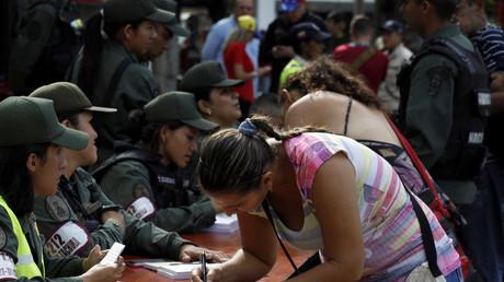 Une femme remplit un formulaire devant des soldats vénézuéliens au niveau du pont Simon Bolivar, à la frontière entre la Colombie et le Venezuela (image d'illustration).