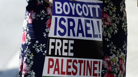 Jeune femme portant une pancarte incitant au boycott des produits israéliens (image d'illustration).