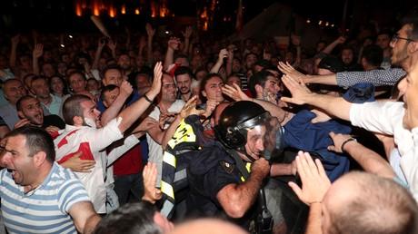 Des manifestants encerclent un policier lors d'une manifestation contre le discours d'un député russe au parlement géorgien, à Tbilissi, le 20 juin 2019.