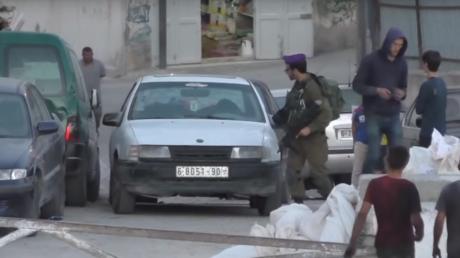 Un soldat israélien frappe des voitures de palestiniens avec son arme à feu