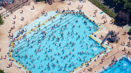 Photo aérienne prise le 30 juin 2019 montrant des personnes au bord d'une piscine extérieure du quartier berlinois de Mariendorf, en Allemagne (image d'illustration).