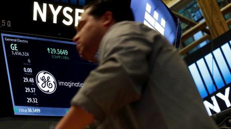 Un trader passe devant un écran affichant la cotation de l'action du groupe General Electric à la Bourse de New York (NYSE), le 31 octobre 2016. Depuis cette photo, le cours de l'action a presque été divisé par quatre (illustration).