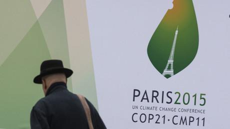 Un passant marche devant des affiches du Sommet mondial sur le climat de la COP 21 à Paris, en 2015.