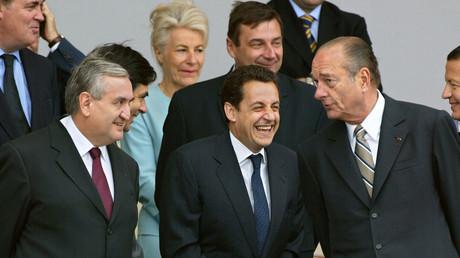 le président Jacques Chirac (D) s'adresse au ministre de l'Intérieur Nicolas Sarkozy (C) sous le regard du Premier ministre Jean-Pierre Raffarin (G), à la tribune officielle place de la Concorde à Paris, lors du traditionnel défilé militaire de célébration de la fête nationale.