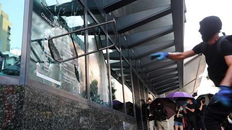 Un manifestant casse la vitre d'un bâtiment gouvernemental lors d'une manifestation à Hong Kong le 1er octobre.