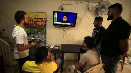 Des jeunes gens regardent le chef du Hezbollah libanais Sayyed Hassan Nasrallah lors de son discours diffusé à la télévision depuis un café situé dans la ville portuaire de Sidon, au Liban, le 25 octobre 2019.