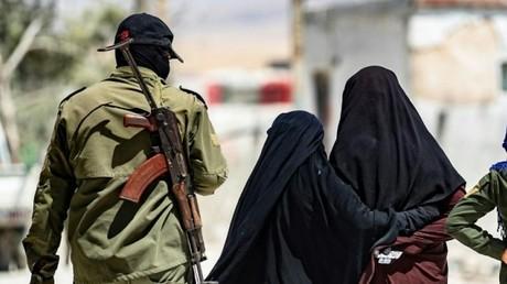 Des proches de djihadistes escortées par des gardes armés le 23 juillet 2019 dans le camp de déplacés de al-Hol, dans le nord-est de la Syrie.
