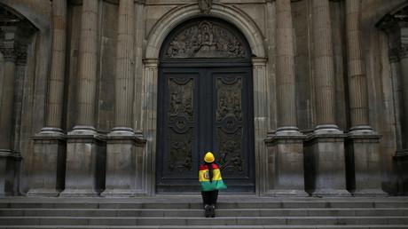 Une femme enveloppée du drapeau bolivien prie devant la cathédrale de La Paz, après l'annonce de la démission d'Evo Morales, le 10 novembre 2019.