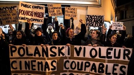 Des manifestants brandissent des banderoles lors d'une manifestation contre le réalisateur franco-polonais Roman Polanski devant une salle de cinéma à Paris le 12 novembre 2019.