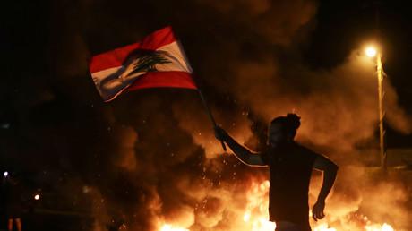 Un manifestant brandit le drapeau libanais devant une route reliant la ville de Tripoli à Beyrouth, le 13 novembre 2019.
