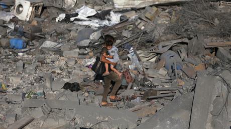 Un garçon palestinien porte son frère alors qu'il marche sur les ruines d'une maison détruite lors d'une frappe aérienne israélienne dans le sud de la bande de Gaza, le 14 novembre 2019.