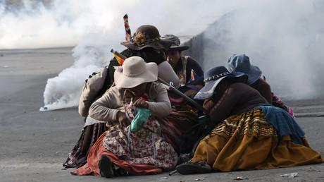 Des femmes indigènes boliviennes se protègent des gaz lacrymogènes lors d'une manifestation contre le gouvernement intérimaire à La Paz, le 15 novembre 2019.