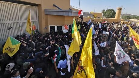 Des manifestants et membres d'une milice armée protestent devant l'ambassade américaine à Bagdad contre des frappes américaines, le 31 décembre 2019.