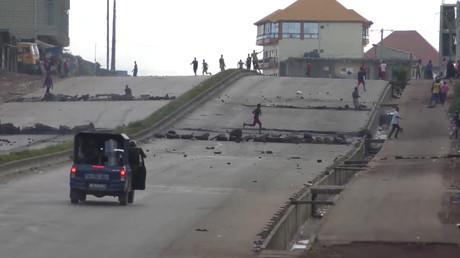 Des manifestants jettent des pierres sur un véhicule de la police anti-émeute dans le quatier de Sonfonia à Conakry, le 14 octobre 2019 (image d'illustration).