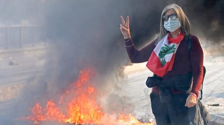 Une manifestante libanaise anti-gouvernement fait le signe de la victoire à côté d'un barrage routier en feu dans la capitale, Beyrouth, le 14 janvier 2020.