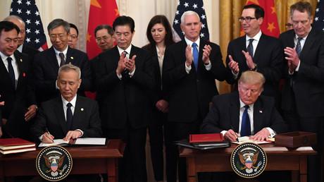 Le vice-premier ministre chinois Liu He (g.) et le président américain Donald Trump (d.) signent l'accord commercial dit de «première phase» entre les Etats-Unis à la Maison Blanche à Washington, le 15 janvier 2020