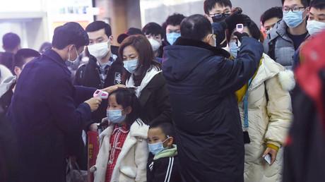 Les membres du personnel vérifient la température corporelle des passagers après l'arrivée d'un train en provenance de Wuhan à la gare de Hangzhou, dans la province orientale du Zhejiang en Chine, le 23 janvier.