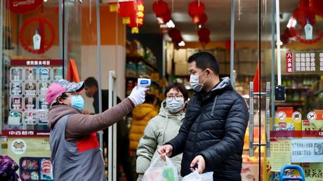 Une personne prend la température de clients qui sortent d'un supermarché, le 7 février à Wuhan, en Chine.