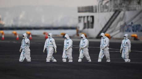 Des personnes portant des combinaisons de protection quittent le bateau de croisière Diamond Princess, avec environ 3 600 personnes mises en quarantaine à bord en raison des craintes du nouveau coronavirus, dans le port de Yokohama, au Japon, le 10 février 2020.