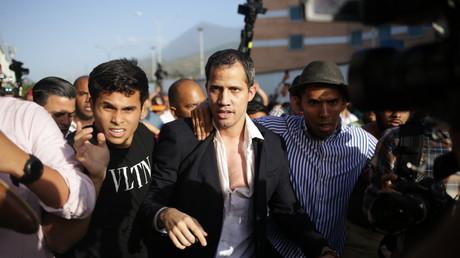 Le chef de l'opposition vénézuélienne et président par intérim autoproclamé Juan Guaido est escorté jusqu'à sa voiture après son arrivée à l'aéroport international Simon Bolivar de Maiquetia, dans l'Etat de Vargas, au Venezuela, le 11 février 2020 (image d'illustration).