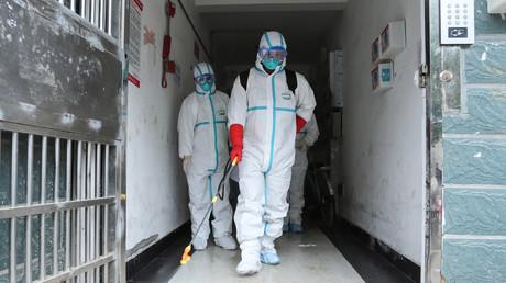 Cette photo prise le 25 janvier 2020 montre des membres du personnel portant des vêtements de protection désinfectant un quartier résidentiel à Ruichang, dans la province centrale du Jiangxi en Chine à côté de la province du Hubei (image d'illustration).
